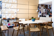 Chairs around a table in an office space, a corkboard in the background