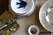 Stacks of porcelain plates, pewter serveware, and tarnished cutlery atop striped napery