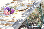 An outdoor table decorated with flowers and a striped table runner.