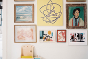 A gallery wall of art and framed portraits