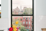 A kitchen window with a colorful floral arrangement sitting beside it.