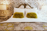 Floral wallpaper in a room with an ornate upholstered headboard and acrylic bedside tables