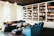 A gray couch and blue armchairs beneath rustic wood beams