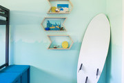 Teal and blue kid's bedroom with white surfboard.