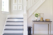 Small table with minimal decor in this all-white stairway.