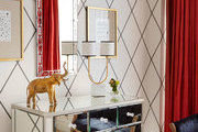 Mirrored dresser and bright decor against striped wallpaper.