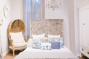A shabby chic bedroom with carved headboard and chandelier.