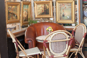 In Savannah's Paris Market, a café table surrounded by framed art
