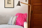 A hot pink pillow tucked in a living room sofa