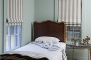 Striped Roman shades and twin beds set foot-to-foot in a Hamptons guest room