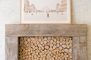 Large framed photo above perfectly packed firewood storage.