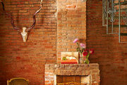 A brick hearth and spiral staircase in the living room of a historic New Orleans home