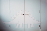 A dinosaur mural on closet doors