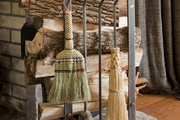 Fireplace tools and logs of wood organized atop a stone hearth