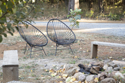 Acapulco chairs are arranged in front of an outdoor fire pit.