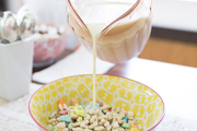 A detail of milk being poured into a cereal bowl.