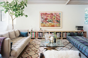 A glass coffee table surrounded by midcentury furniture and a Moroccan rug
