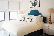 A blue upholstered headboard accented by white bed linens