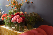A tufted red settee beside a table filled with vases of flowers in a floral studio.