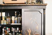 A chinoiserie cabinet of bar essentials topped with decorative objects