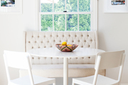 A neutral dining nook with a tufted bench.