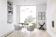 A contemporary workspace with a Saarinen table and floor-to-ceiling window