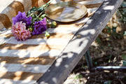 An outdoor table with flowers and a striped table runner.