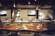 A wooden dining table and white chairs at ABC Kitchen