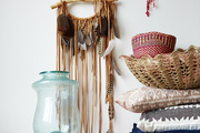 A dream catcher hung beside a stack of baskets, books, and pillows on a wooden console table