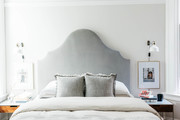 A neutral bedroom with a gray headboard and beige bedding.