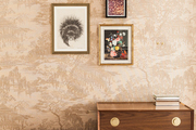 A grouping of art hung on wallpapered walls