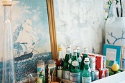Bar essentials on a tray and a framed nautical artwork on a wooden dining sideboard