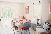 A polka-dotted Cath Kidston tablecloth, Union Jack pillow, and Paddington Bear decorate a classic English-country-style dining room.