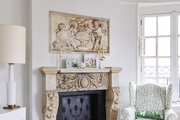 Elegant beige fireplace with matching art in white living room.