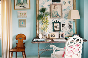 An office space with a white loop chair and an inspiration board with a floral pattern