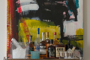 A detail of a bar cart with an abstract painting.