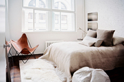 A leather butterfly chair and gray and beige bedding in a neutral bedroom