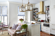 Gold framed lights hanging over kitchen island.