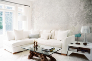 Nature-inspired wallpaper behind a white sectional couch