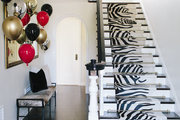 In this entryway, an animal print lined stairway is at the center of a flashy space.