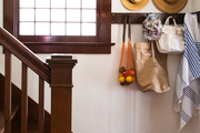 Hats and bags hung on hooks in an entry near a staircase