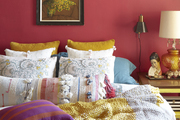 A bold statement wall complimented with multi fabric and colored bed sheets and pillows.