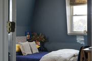 A dark blue bedroom highlights a Tom Dixon beat pendant and mixed bedding.