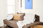 A sofa with a fringe throw blanket and patterned pillows sitting on top.