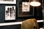A vintage black floor lamp beside a gallery wall of art