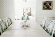 A chandelier adorned with shells in a dining space with walls covered in lattice