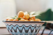 A blue patterned bowl of kumquats