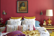 Throw pillows with tassels are arranged in a bedroom with red walls.