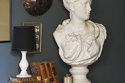 A marble bust, old books, and artwork against a moody wall