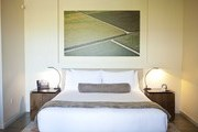 A guest bed under a contemporary artwork at Napa Valley's Bardessono hotel
